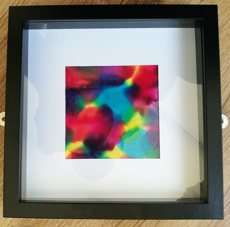 A small square   piece of Japanese Silk with abstract shapes and patterns in all the colours of the rainbow. Mounted with a thick border of white card and a deep black square frame
