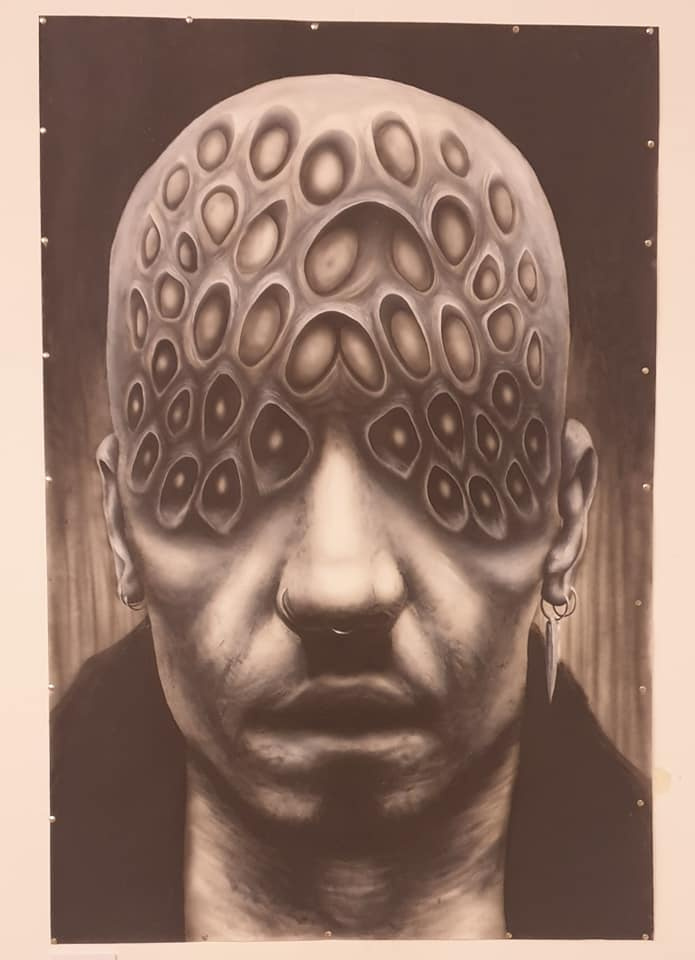 A black and white painting showing a surreal male face covered in strange orb shapes from the eye level up onto a bald head